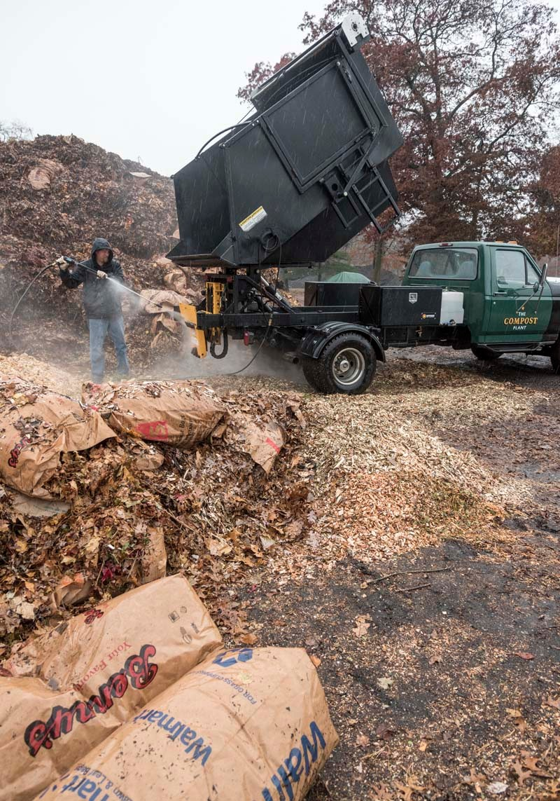 CLEAN AND GREEN: Nat Harris washes The Compost Plant's truck after food scraps were dumped on a compost pile at Earth Care Farm in Charlestown. / PBN PHOTO/MICHAEL SALERNO
