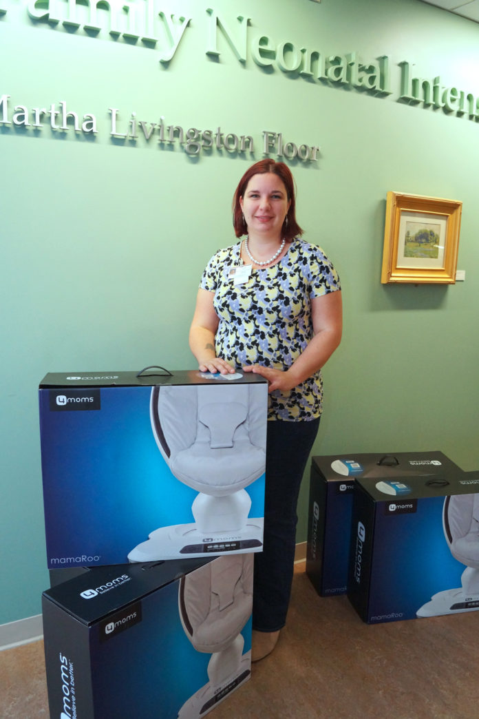 Corin Nava, co-founder of the national nonprofit Project Sweet Peas, stands recently with a donation of Mamaroo swings for infants for the Women & Infants Hospital of Rhode Island.                    / Women & Infants Hospital of Rhode Island