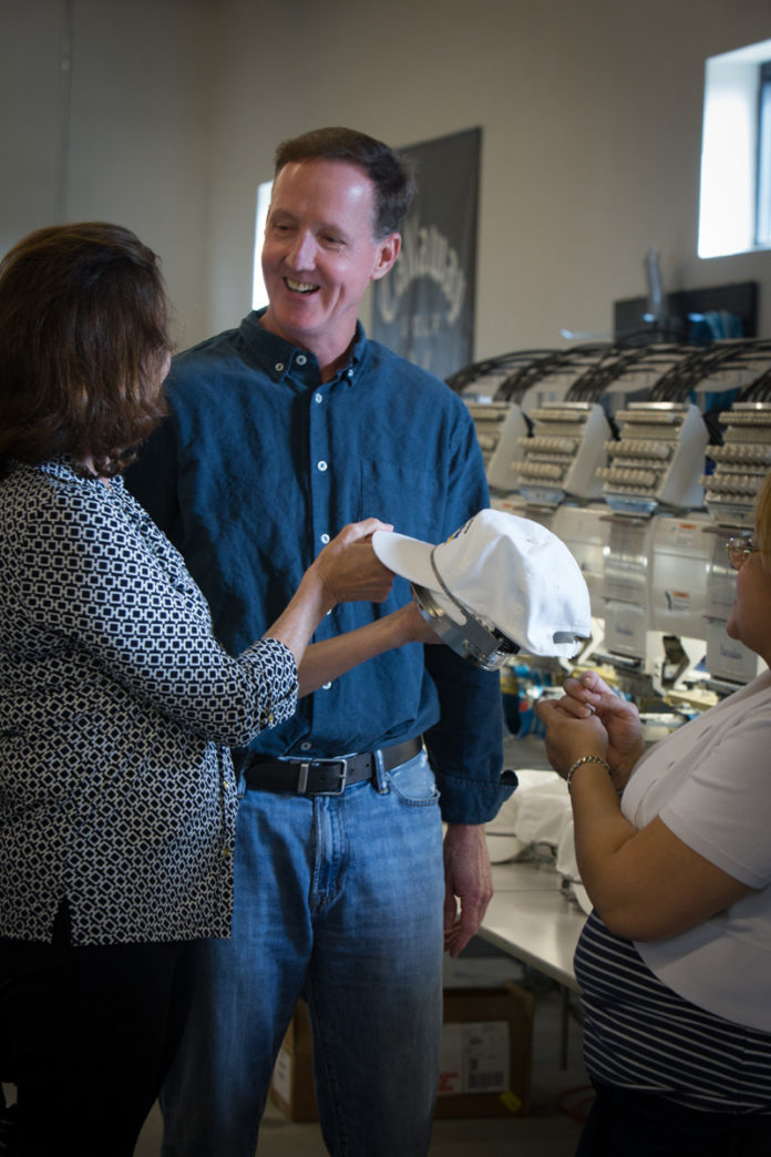 THOMAS KELLOGG III and his wife Leslie look at one of the hats they embroider at their business, ParsonsKellogg LLC, with employee Adriana Escobar. Kellogg was named Rhode Island's Small Business Person of the Year by the U.S. Small Business Administration. / PBN FILE PHOTO/STEPHANIE ALVAREZ EWENS