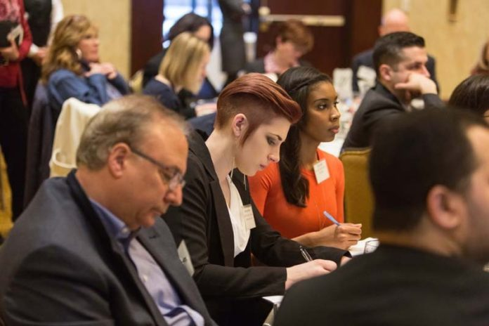 """EXPERT ADVICE: Attendees take notes during the Providence Business News summit on """"Growing and Protecting Your Brand"""" Feb. 25 at the Crowne Plaza Providence-Warwick. / PBN PHOTO/RUPERT WHITELEY"""