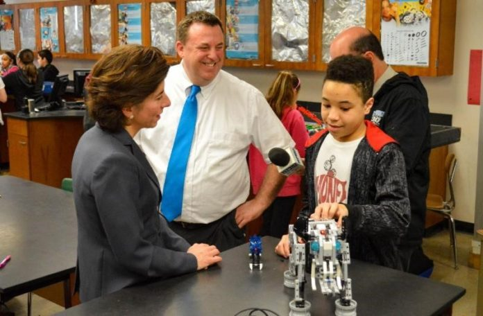 GOV. GINA M. Raimondo speaks with a student in Thomas Hargreaves' robotics class about the robotic elephant he created. / COURTESY GOVERNOR'S OFFICE