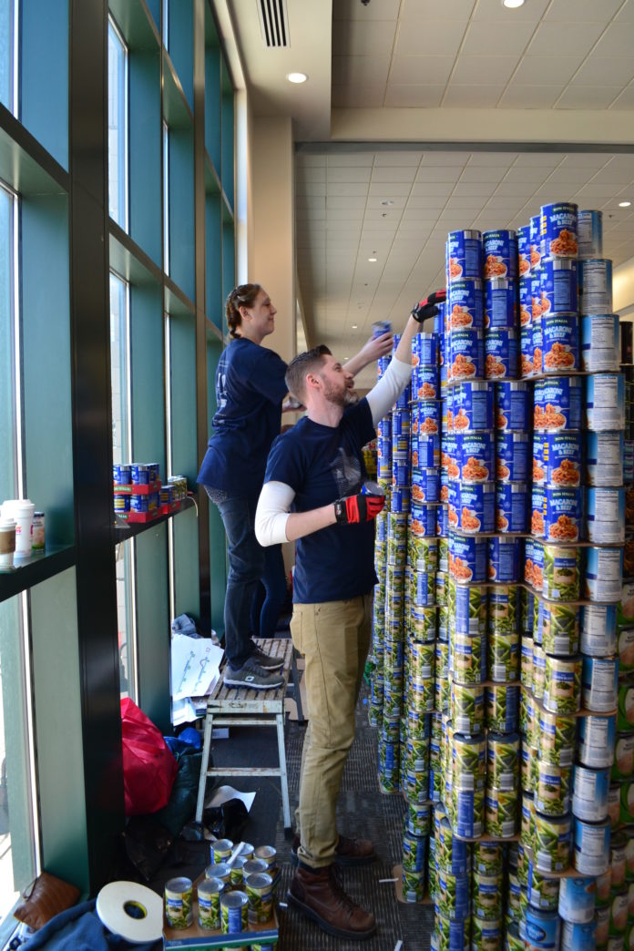 """Kristine Christensen, left, and Pierson Booher, both employees of Durkee, Brown, Viveiros & Werenfels Architects of Providence, build the indoor seawall for the sculpture """"Turning the Tides On Hunger"""" with their teammates. The event March 12 involved six teams and took place at the Providence Place Skybridge Concourse during Canstruction Build Day to collect canned food for the Rhode Island Community Food Bank. / COURTESY RHODE ISLAND COMMUNITY FOOD BANK"""