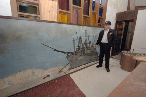 JIM RUGH looks at a mural depicting Seabees unloading supplies at a station in Antarctica. / PBN FILE PHOTO/BRIAN MCDONALD
