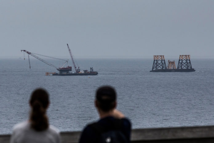 PEOPLE LOOK out at a Deepwater Wind LLC offshore wind farm under construction off the coast of Block Island in July 2015. / BLOOMBERG NEWS FILE/SHIHO FUKADA