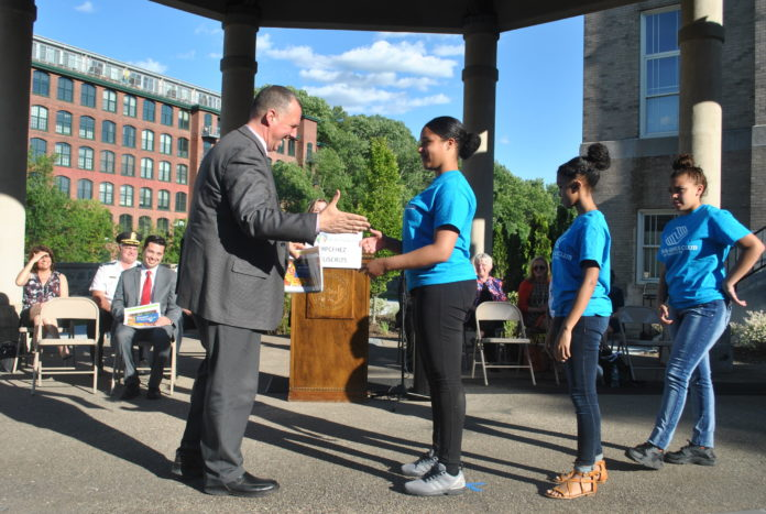 Pawtucket Mayor Donald Grebien accepts a copy of the Building Healthy Neighborhoods Action Plan from Pawtucket Boys & Girls Club Keystone Club Members Anna Gomes, Arizella Baptista and Serenity Perry.  . / COURTESY LISC RHODE ISLAND