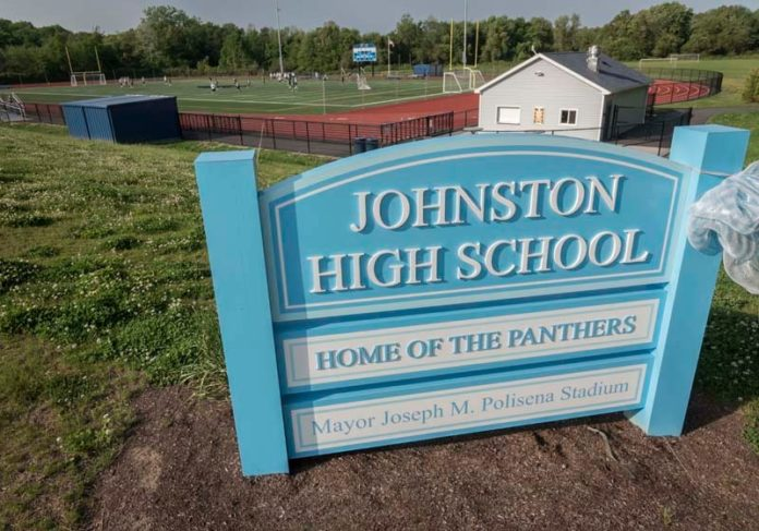 IGNORING WARNING SIGNS? A sign bearing the name of Johnston Mayor Joseph M. Polisena is seen at the town's high school. Johnston in 2013 settled a lawsuit with R.I. Resource Recovery Corp. and received $3 million. But unlike East Providence and North Providence, local lawmakers decided to spend the sudden influx of cash on a new athletic complex, named for the mayor, instead of its ailing pension system. / PBN PHOTO/MICHAEL SALERNO