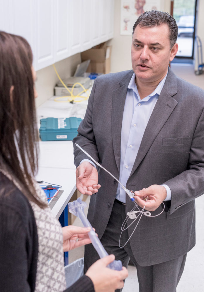 MANNY AVILA, president and CEO of IlluminOss Medical, is shown speaking with Amy O. Berman, vice president, clinical affairs, in the lab. Berman is holding a model of a bone and Avila has the IlluminOss implant that is inserted inside the bone and then hardened using light.