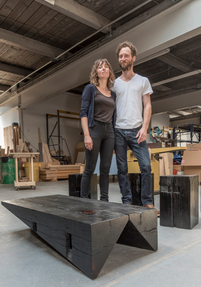 CREATIVITY IGNITED: Anastasia Laurenzi and Michael Larsen are partners in Oblique Studios LLC. Some of their creations include the scorched-wood coffee table in front of them and a Southern yellow pine bench, below. / PBN PHOTOS/MICHAEL SALERNO