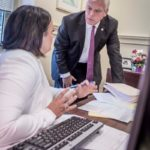PROACTIVE APPROACH: Warwick Mayor Scott Avedisian speaks with his press secretary, Courtney Marciano, at his office. Avedisian suggested creating a statewide OPEB trust to help small local plans. / PBN PHOTO/MICHAEL SALERNO