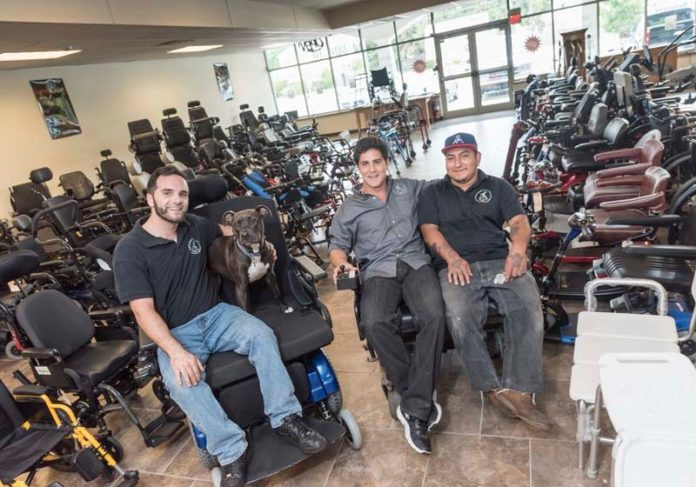 ON A GOOD ROLL: Mobility Equipment Recyclers accepts donations of new and used mobility medical devices and equipment, including powered wheelchairs, for resale at a discount. From left are Andrew Celani, store manager, Bailey, company mascot, John Perrotti, owner and Raymond Perez, technician. / PBN PHOTO/MICHAEL SALERNO