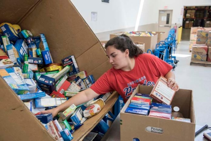 HELPING HAND: Ashley Armstrong of Warwick sorts donated foods at the Rhode Island Community Food Bank. It was Armstrong's first day volunteering at the food bank, part of the charitable work she needs to do in order to make her confirmation at Saints Rose and Clement parish in Warwick. / PBN PHOTO/ MICHAEL SALERNO