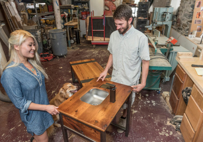 REFINED RECYCLING: Christian T. Descoteaux, right, and Huetran Duong run Christian Thomas Designs LLC. Shown are a vanity made from reclaimed fir and polished steel and a table of reclaimed hard pine beams wrapped in hollow steel. / PBN PHOTO/MICHAEL SALERNO