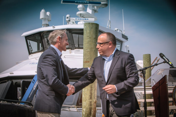 THE R.I. Division of Public Utilities and Carriers on Thursday approved an application filed by Rhode Island Fast Ferry Inc. asking permission to provide high-speed ferry service between Quonset Point, North Kingstown, and Old Harbor, Block Island. Charles A. Donadio Jr., president of Rhode Island Fast Ferry, left, shakes hands with Jeffrey Grybowski, CEO of Deepwater Wind LLC, at an event recently. / COURTESY TRIPP BURMAN PHOTOGRAPHY