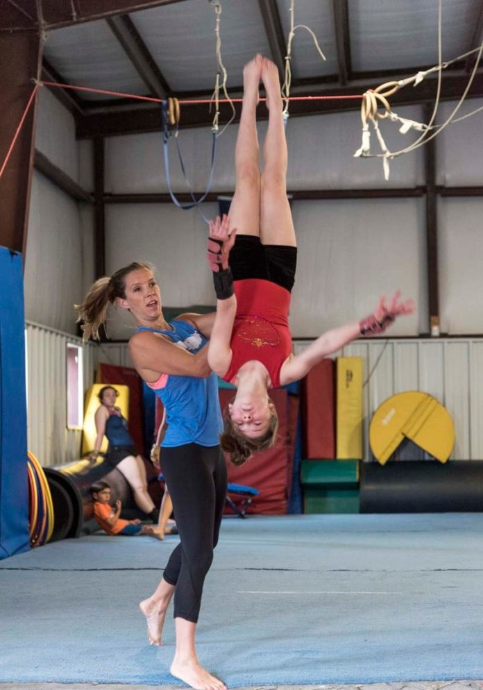 IN THE BALANCE: Shannon Hughey Cornicelli, founder and owner of Dream Big Academy, is seen spotting gymnastics student Emily Pacillo, 12. / PBN PHOTO/MICHAEL SALERNO