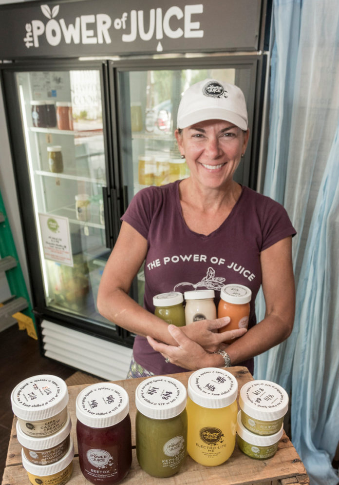 BACK TO BASICS: Brigid A. Rafferty, owner of The Power of Juice, a juice company focused on improving people's health using unprocessed ingredients, displays some of her products. / PBN PHOTO/MICHAEL SALERNO