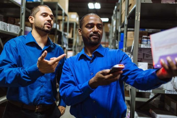 SIMPLE YET POWERFUL: Demonstrating Claflin 360, a handheld  inventory-control device the company rolled out in April 2015, are Jonathan Buchanan, left, Claflin Co. network manager, and Tony Suchite, IT operations manager. / PBN PHOTO/RUPERT WHITELEY