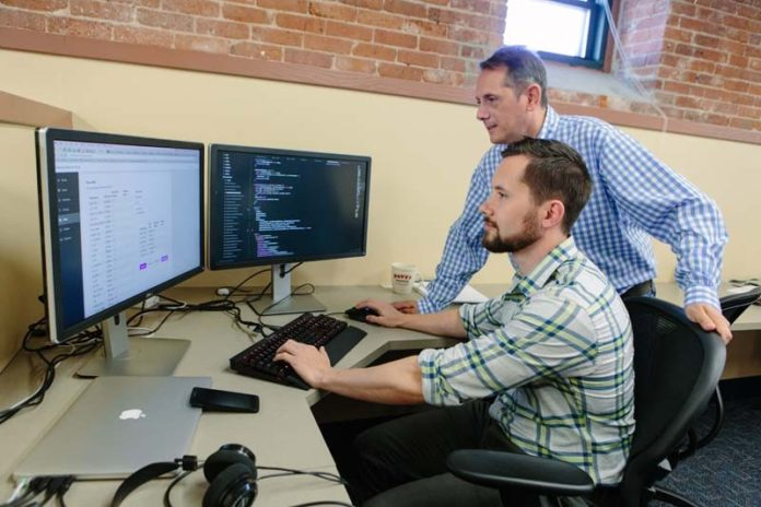 IN THE RIGHT PLACE AT THE RIGHT TIME: Datarista founder and CEO Pat Sabatino, standing, has had no problem finding the right talent in Providence, including Dave Counts, senior front-end engineer for the cloud-based, data-management startup. / PBN PHOTO/RUPERT WHITELEY