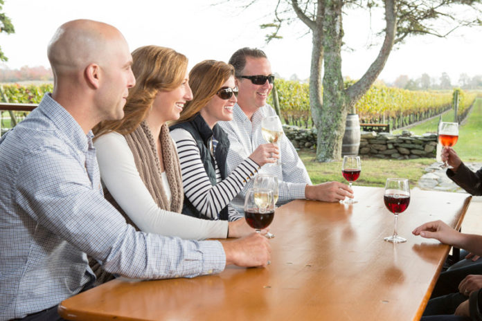 LOCAL  FLAVOR: Couples enjoy an outdoor wine tasting at Newport Vineyards, one of 14 vineyards and wineries that make up the Coastal Wine Trail in Southern New England. / COURTESY MARIANNE LEE PHOTOGRAPHY