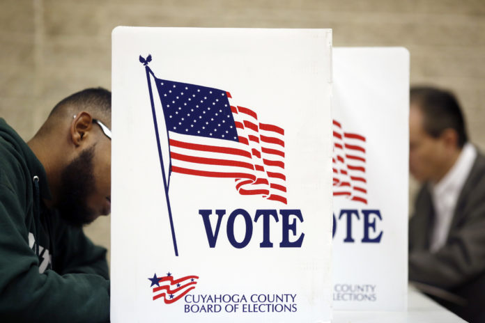 VOTERS CAST ballots at the St. Thomas More polling location in Cleveland on Nov. 8. The Justice Department will deploy 500 personnel to polling stations, including those in Providence and Pawtucket, on Election Day to help protect voters against discrimination and intimidation. / BLOOMBERG NEWS PHOTO/LUKE SHARRETT