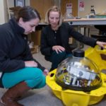 NAVY TECH: MIKEL President Kelly Mendell, right, looks at a beacon in the prototype lab with software engineer Kayla Gandolfi. The company recently announced a  $23 million U.S. Navy contract for developing  advanced sonar and sensors technology. / PBN PHOTO/KATE WHITNEY LUCEY