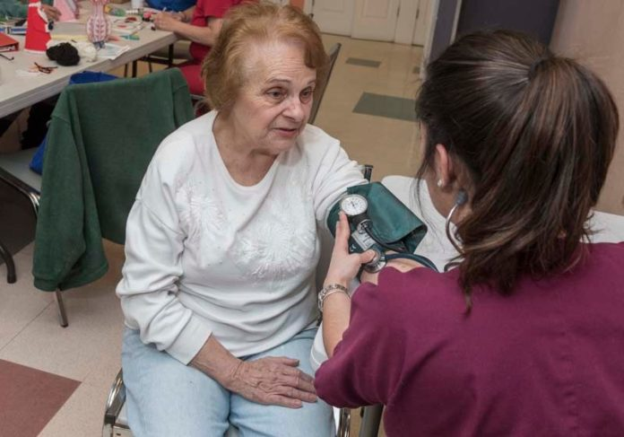HEALTH CHECK: RIC nursing student Jaclyn Baribault measures Nazareth Cabral's blood pressure at the Leon Mathieu Senior Center in Pawtucket. / PBN PHOTO/ MICHAEL SALERNO
