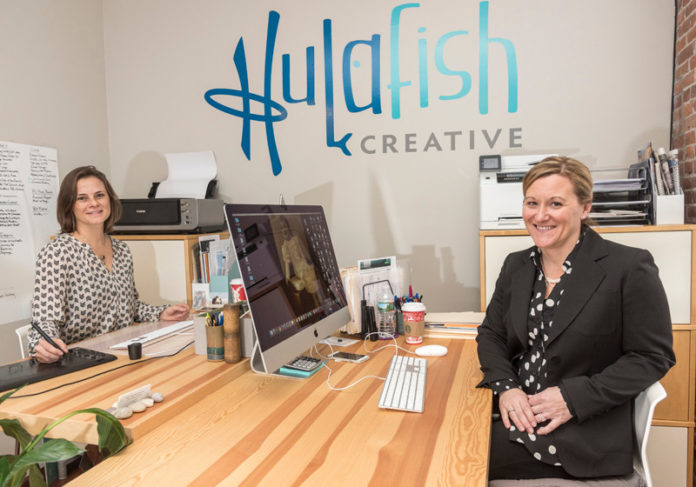 DESIGN DUO: From left, Jamie Sharp, graphic designer, and Jennifer Giardino, marketing strategist, owners of Hulafish Creative in North Kingstown, which creates marketing campaigns and logos. / PBN PHOTO/ MICHAEL SALERNO
