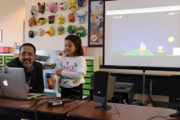 TIMOCCO INC. CEO Eran Arden shows Mia Izzi Pirotto how to use the company's latest therapeutic gaming technology that allows users to practice more complex hand and wrist movements while playing games online. The game used motion-based technology to track the movements for children with special needs. Timocco has been testing the game with students and staff at Providence's Meeting Street school as well as with faculty from Brown University and Hasbro Children's Hospital. / COURTESY TIMOCCO INC.