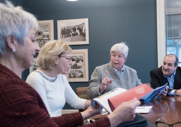ANNUAL REPORT: URI Foundation members go over the new 2016 annual report in the Alumni Center. From left, Rita A. Verespy, director of gift planning; Lil Breul O'Rourke, president; Deborah Imondi, Investment Committee chair; and Adam Quinlan, chief financial officer. / PBN PHOTO/ MICHAEL SALERNO