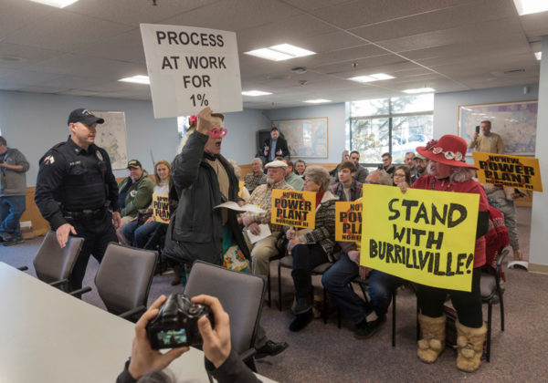 """VOCAL OPPOSITION: During a R.I. Public Utilities Commission hearing before the R.I. Energy Facility Siting Board concerning the proposed Burrillville power plant, URI physics professor Peter Nightingale, a member of Raging Grannies of Greater Westerly, holding his sign, """"PROCESS AT WORK FOR 1%,"""" was ejected for vocally protesting. / PBN PHOTO/MICHAEL SALERNO"""