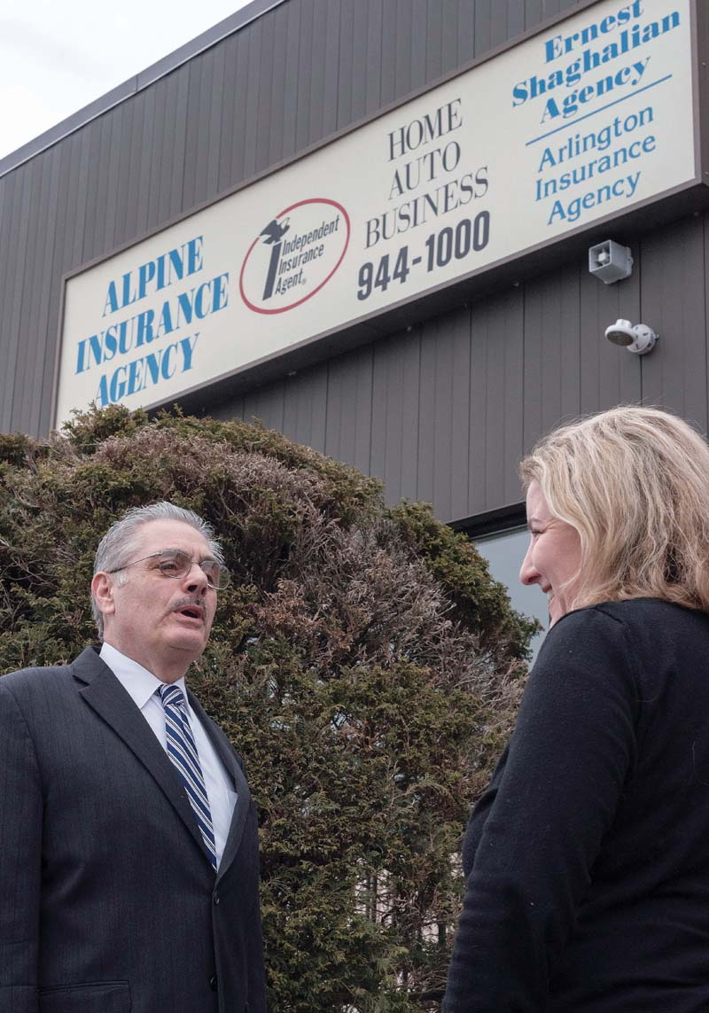 CONCERNED AGENT: Ernest Shaghalian Jr., owner of Alpine Insurance Agency in Cranston, talks with Mary-Margaret Trigo, client-services representative. Shaghalian is concerned owners aren't currently covered by insurance when their cars are used for ride-hailing purposes in Rhode Island. / PBN PHOTO/MICHAEL SALERNO