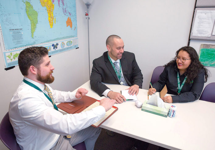 ON A MISSION: From left, Neighborhood Health Plan of Rhode Island officials Ed Curis, policy analyst; David Burnett, chief of staff; and Ericka Moore, sales and marketing representative, meet at the nonprofit's Providence office. / PBN PHOTO/TRACY JENKINS