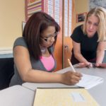 HELPING HAND: Amanda Hanley, right, transition councilor for Rhode Island Regional Adult Learning, assists Esther Alvarez, of Woonsocket, as part of an adult-education class for workers learning English skills. / PBN PHOTO/MICHAELSALERNO