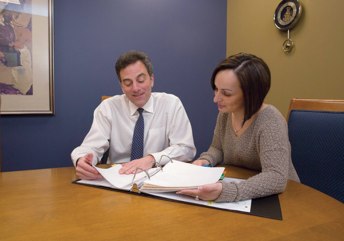 IN DEMAND: Michael Bigney, administrator and co-owner, Home Health & Hospice Care of Nursing Placement, goes over paperwork with Kari Raposa, a registered nurse and hospice clinical manager, at the hospice center in Pawtucket.  / PBN PHOTO/TRACY JENKINS