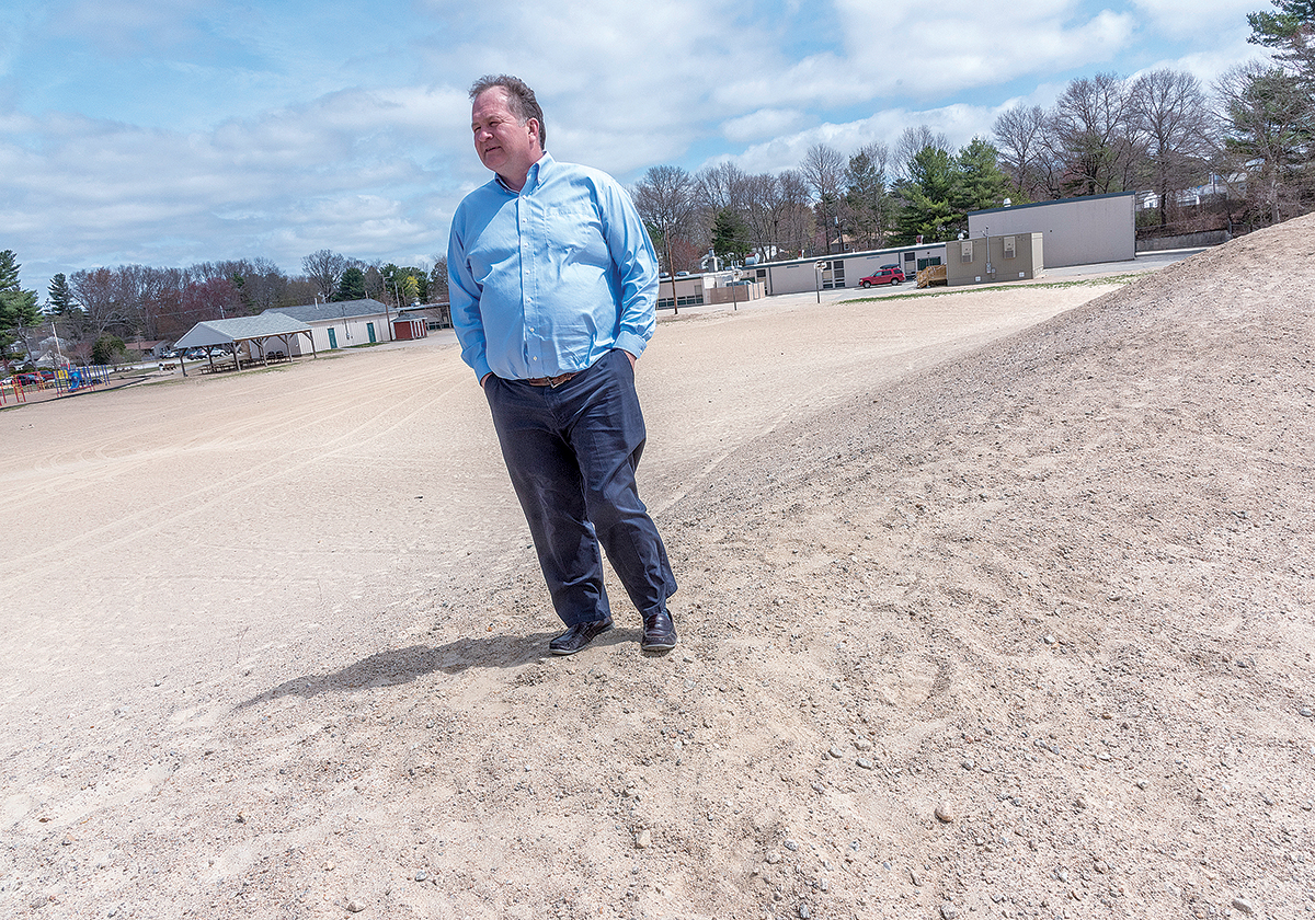 SANDSTORM: Coventry School Superintendent Craig Levis stands on the slope of the dunes of a giant sand pit behind the Hopkins Hill Elementary School in Coventry, where soil was taken for the Centre of New England development. On windy days, children must be kept off the play area because it gets sandblasted. / PBN PHOTO/­MICHAEL SALERNO