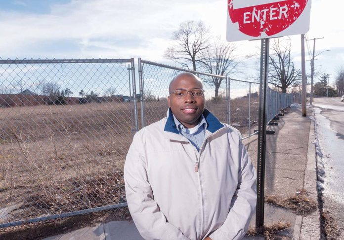 CLEARED TO BUILD: Dwayne Keys, chairman of the South Providence Neighborhood Association, stands outside the former Flynn Elementary School on Blackstone Street, where a developer has proposed a $30 million to $40 million mixed-use project. / PBN PHOTO/MICHAEL SALERNO