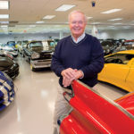 IMPRESSIVE COLLECTION: Gunther Buerman, who is set to open the Newport Car Museum this summer, stands among his personal collection of classic cars. / PBN PHOTO/KATE WHITNEY LUCEY