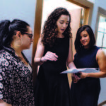 PURPOSEFUL ACHIEVEMENT: Libby Kimzey, center, the Capital Good Fund's chief operating officer, is instrumental in the nonprofit lender's success, including expanding its offices. Here, she confers with loan officers Heiry Bulux, left, and Vanessa Ramirez. / PBN PHOTO/RUPERT WHITELEY