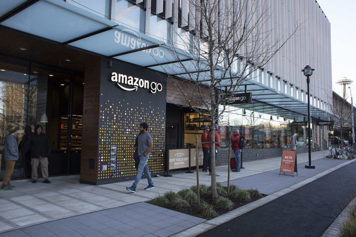 A PEDESTRIAN PASSES in front of the new Amazon Go grocery store in Seattle. The retail giant unveiled technology that will let shoppers grab groceries without having to scan and pay for them - in one stroke eliminating the checkout line.