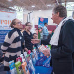 LISTENING: Endeavoring to promote the state's small-business community, Lt. Gov. Daniel McKee, right, hosted a discussion at the 6th Annual Latino Business Expo. Here, McKee talks with, from left, Maria Sol Cuesta and Marleny Perez, bilingual benefit specialists at The Point. / PBN PHOTO/­MICHAEL SALERNO