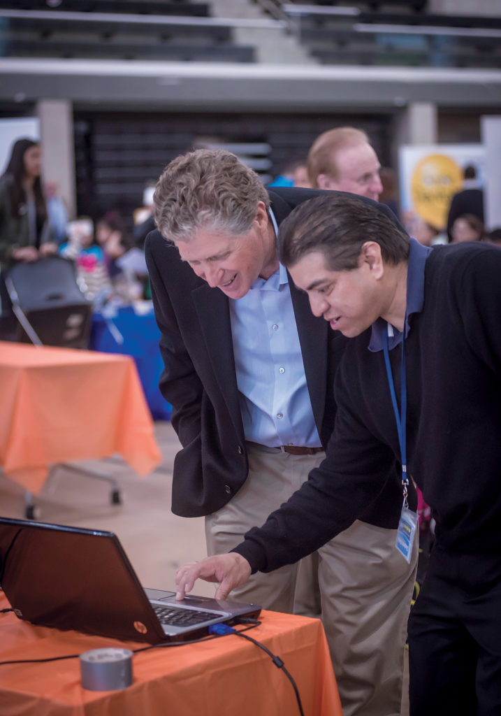 LT. GOV. Daniel McKee, left, in 2017 looks at the website of Chapincito Media, a multimedia production company, with owner Edwin Arroyo Mendez. / PBN FILE PHOTO/MICHAEL SALERNO