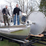 SHIPSHAPE: BluSource Energy owner Thomas Derecktor, right, and Michael Miller, a mechanical engineer with BluSource Energy, onboard Joule, a pontoon vessel with hydrokinetic turbines built for Brown University. / PBN PHOTO/KATE WHITNEY LUCEY