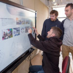 NEW TECH: Jeremy Wise, sitting, of Hillsbrough, N.J., uses an interactive touch screen to show Christian Caldwell, standing left, of Barnstable, Mass., and Matt Aiello, of Shrewsbury, Mass., a project he designed for an innovation center in Roxbury, Mass. All are fifth-year students in the master of architecture program at Roger Williams University. / PBN PHOTO/KATE WHITNEY LUCEY