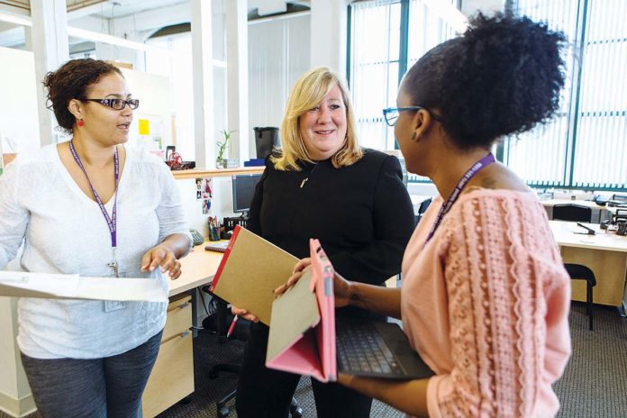 HELPING CLIENTS: Margaret Holland McDuff, center, CEO of Family Service of Rhode Island, says her time as a social worker informs her management approach. Here, she speaks with Elizabeth Ferreira, left, and Gloria Molero. / PBN PHOTO/RUPERT WHITELEY