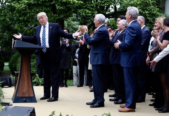 U.S. President Donald Trump, left, speaks as U.S. Vice President Mike Pence, center, applauds during a press conference in the Rose Garden of the White House in Washington, D.C., U.S., on Thursday. House Republicans mustered just enough votes to pass their health-care bill Thursday, salvaging what at times appeared to be a doomed mission to repeal and partially replace Obamacare under intense pressure from Trumpto produce legislative accomplishments. / BLOOMBERG / ANDREW HARRER