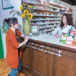 MODERN CLASSIC: Pharmacist Christina Procaccianti, right, operates a modern version of a classic American drugstore. Green Line Apothecary is on Main Street in South Kingstown. Above, she talks with Laura Taylor of Exeter at the drop-off counter. / PBN PHOTO/MICHAEL SALERNO