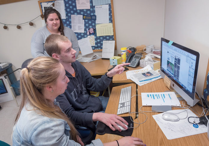 FINAL TOUCHES: The Good 5 Cent Cigar staff at the University of Rhode Island works on the last issue of the semester. Production manager Seamus Fuller points out an online article to managing editor Allie E. Lewis, foreground, while editor-in-chief Emma Gauthier looks on. / PBN PHOTO/MICHAEL SALERNO