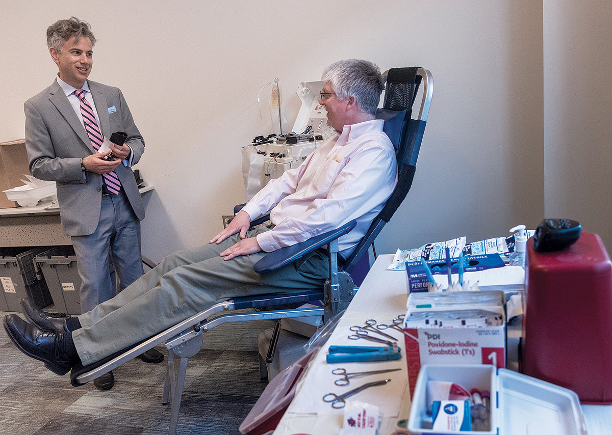 A REGULAR APPOINTMENT: Anthony Bogar, right, of East Providence, gives blood every eight weeks. Following a recent donation at Blue Cross & Blue Shield of Rhode Island offices in Providence, he speaks with Scott J. Asadorian, the Rhode Island Blood Center's vice president and chief operating officer. / PBN PHOTO/MICHAEL SALERNO