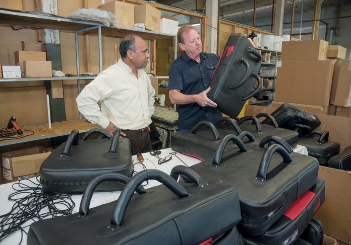 EXPANDING STRENGTHS: John Caito III, right, president of Desmark Industries and its new division, Amerisewn, which designs, engineers and manufactures complex stitched products, speaks with stitcher Alejandro Batz about the body shields they are manufacturing. / PBN PHOTO/MICHAEL SALERNO