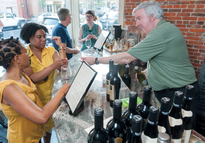 FREE TASTING: John S. Lombardo, right, and Tony Demers are co-owners of Bin 312 on South Main Street in Providence. The wine shop hosts free tastings of off-the-beaten-track wines every Thursday evening. Andrea Nelson, left, foreground, of New York City, and Althea Nelson of Providence taste a rosé from France. / PBN PHOTO/MICHAEL SALERNO