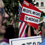 """A DEMONSTRATOR OPPOSED to the Senate Republican health-care holds a sign that reads """"No Cuts, No Caps To Medicaid"""" while marching near the U.S. Capitol in Washington, D.C. on Wednesday. BLOOMBERG FILE PHOTO/ANDREW HARRER"""